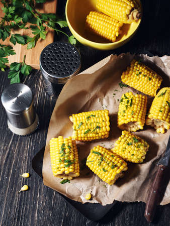 Corn on the cob with chopped parsley and spices.