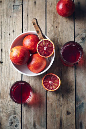 Red orange drink and fresh oranges on a wooden background.