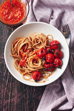 Spaghetti pasta with tomato sauce and roasted cherry tomatoes.