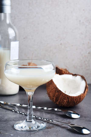Pina Colada liqueur in a glass and coconut halves. Фото со стока