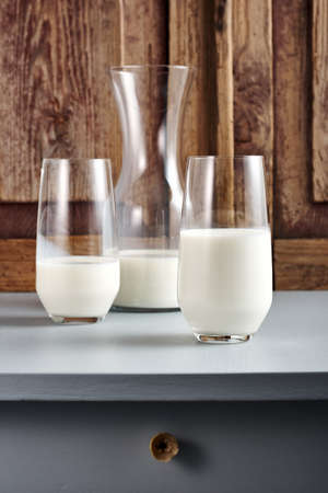 Bottle and two glasses of milk on a wooden table.