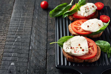 Open sandwiches or bruschetta with mozzarella cheese, tomatoes and basil, caprese on a dark wooden