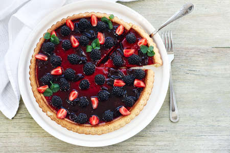 Berry tart with blackberries and strawberries on a wooden table, top view.