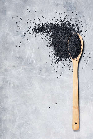 Black sesame seeds in a wooden spoon, top view.