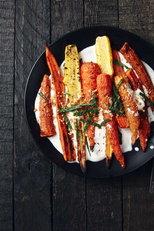 Salad of roasted carrots with yogurt, spices and herbs on a dark background. Фото со стока