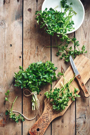 Fresh organic parsley on a wooden rustic background, top view. Фото со стока