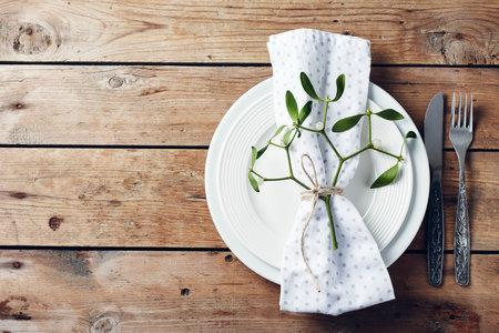 Table setting. White plates, cutlery, napkin and mistletoe.