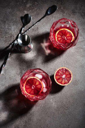 Negroni cocktail with ice cubes and blood orange on a dark gray stone background, top view. Фото со стока