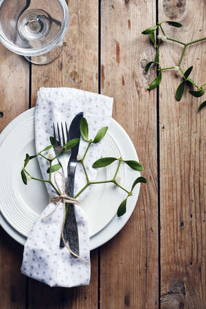 Table setting. White plates, cutlery, napkin and mistletoe on a wooden table. Фото со стока