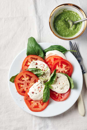 Caprese salad. Tomatoes, mozzarella cheese, basil leaves and pesto sauce.