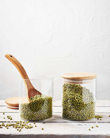 Two glass jars with raw mung beans on a wooden table.