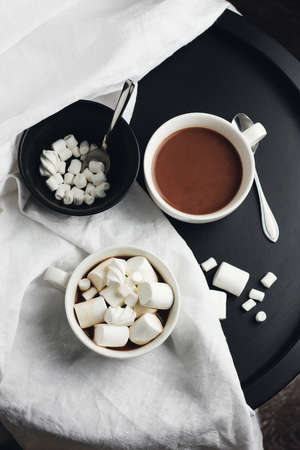 Two cups of hot chocolate, cocoa with marshmallows on a round coffee table.