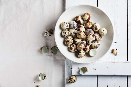 Quail eggs in a bowl on a white table, top view.