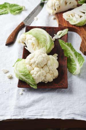 Fresh cauliflower on a white tablecloth, top view.