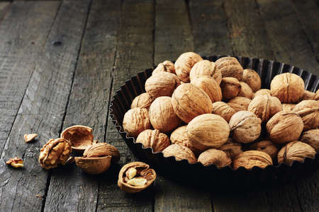 Whole walnuts and kernels on a dark wooden table.