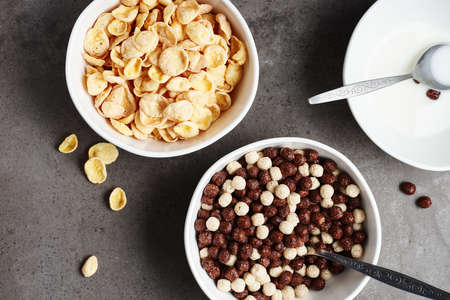 Bowls of breakfast cereals and milk. Cornflakes and chocolate balls. Фото со стока