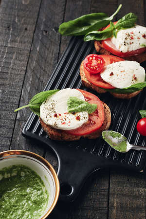 Open sandwiches or bruschetta with mozzarella cheese, tomatoes and basil, caprese on a dark wooden background. Фото со стока