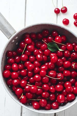 Fresh cherries in colander on a white wooden background.