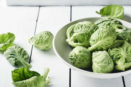 Fresh raw brussels sprouts in a bowl on a white wooden table. Фото со стока