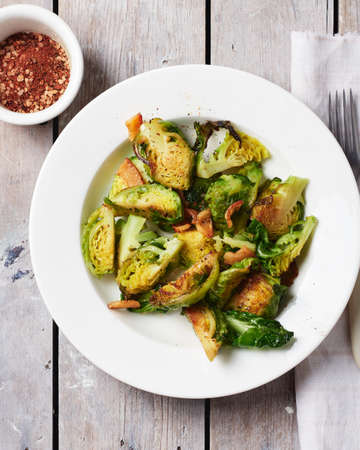 Roasted Brussels sprouts with bacon on a white plate, top view. Фото со стока