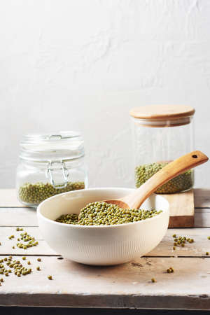 Raw mung beans in a bowl on a wooden table.