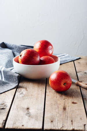 Fresh red blood oranges in a bowl on a wooden table.
