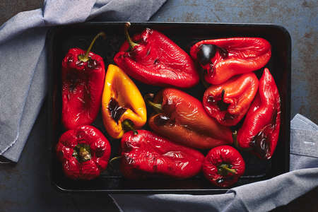Roasted red and yellow peppers in baking tray on a dark background. Top view.