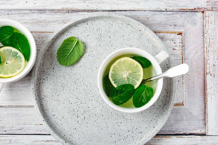 A cup of hot mint tea with lemon on a white wooden table.