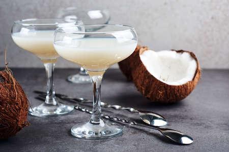 Pina Colada liqueur in a glass and coconut halves. Фото со стока