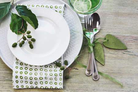 Summer table setting in green tone. Plates, cutlery, napkin and alder branch. Фото со стока