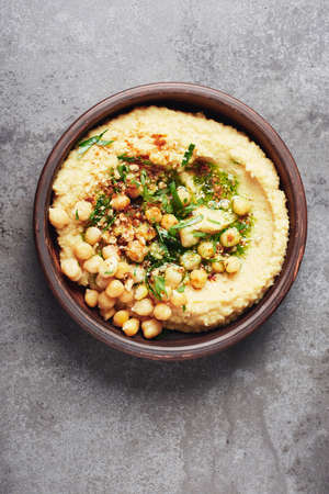 Chickpeas hummus in a bowl on a gray stone background. Top view.