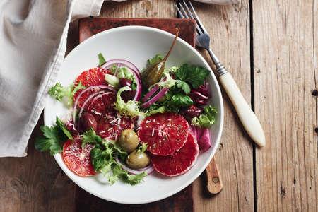 Sicilian orange salad. Salad with blood orange, red onions and olives. Фото со стока