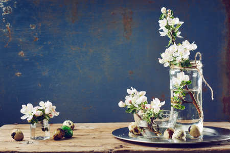Apple blossom flowers, quail eggs on a wooden table. Spring still life.