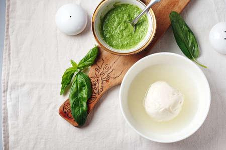 Mozzarella cheese ball in a bowl, pesto sauce and fresh basil leaves.