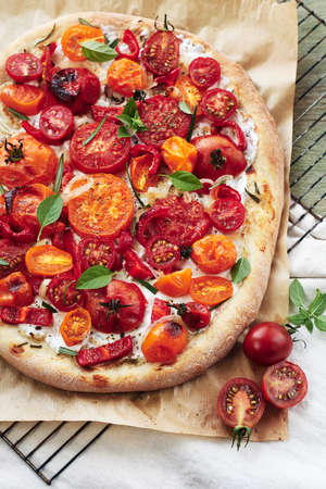 Tomato pizza with cheese and basil on a wooden table.