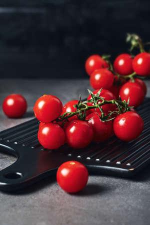 Fresh red cherry tomatoes on the vine. Dark background. Фото со стока