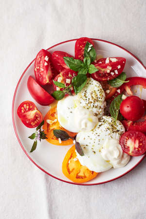 Poached egg and fresh tomatoes with basil and mayonnaise, top view. Фото со стока