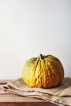 Yellow ripe pumpkin on a wooden table. Halloween concept.