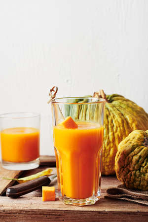 Glass of pumpkin juice, smoothies and ripe pumpkins on a wooden table.