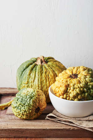 Yellow decorative pumpkins on a wooden table, autumn still life. Фото со стока