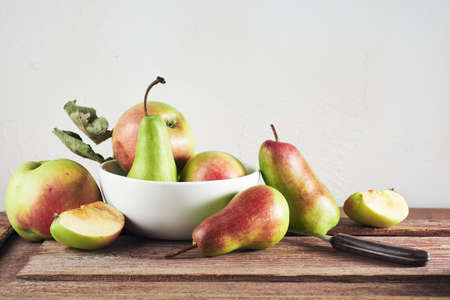 Ripe organic apples and pears on a wooden table, still life. Фото со стока