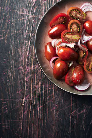 Salad with cherry tomatoes and onions on a dark wooden background, top view.