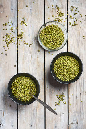 Raw mung beans in bowls on a wooden background, top view.