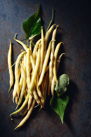 Yellow wax beans on a dark blue background, top view.