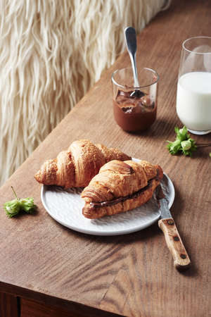 Freshly baked croissants with chocolate cream on a wooden table.