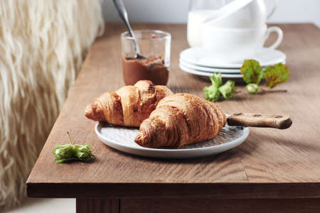 Two croissants with chocolate cream and hazelnuts on a wooden table. Фото со стока