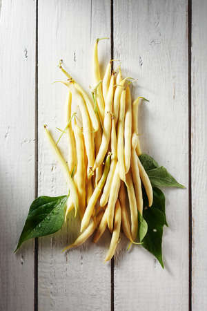 Yellow wax beans on a white wooden table. Фото со стока