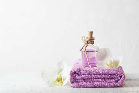 A bottle of lilac perfume and orchid flowers. Aromatic cosmetic product, spa treatments.