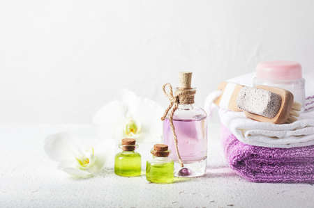 Perfume bottle, oil and orchid flowers. Aromatic cosmetic product, spa treatments.