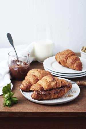 Freshly baked croissants with chocolate cream and hazelnuts. Фото со стока